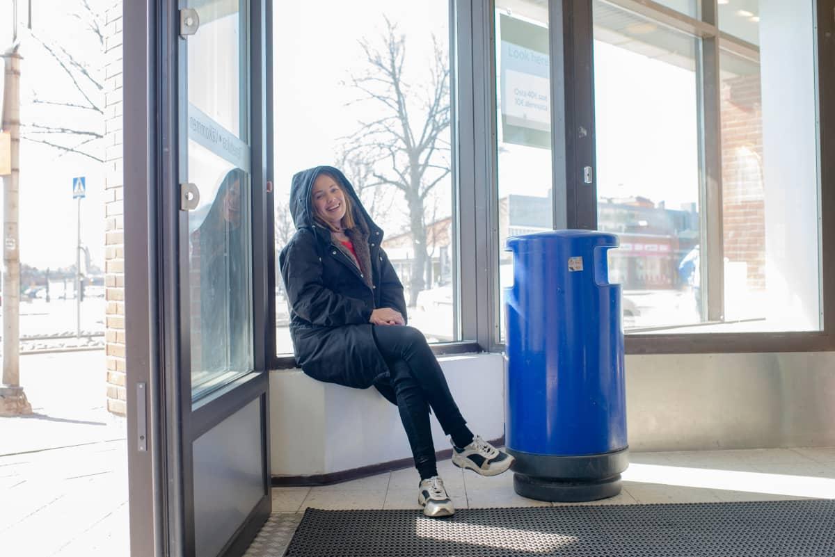 Oona Airola istuu tuulikaapissa ikkunalaudalla.