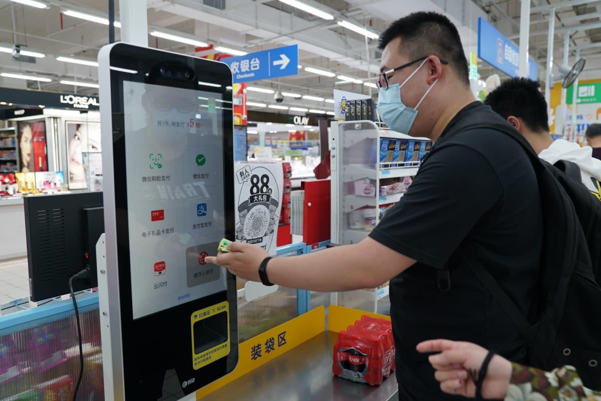 opiskelija He Yanze maksaa ostoksiaan digivaluutalla supermarketin itsepalvelukassalla