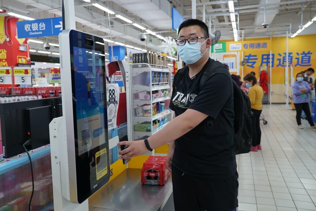 opiskelija Yanze He maksaa ostoksiaan supermarketin itsepalvelukassalla
