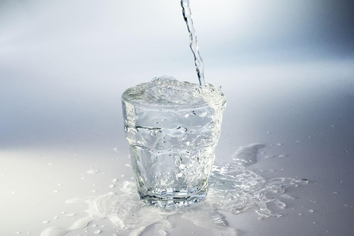 Vettä kaadetaan juomalasiin.