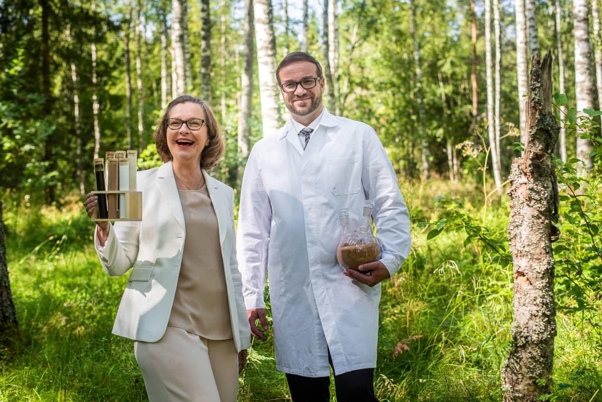 Nainen ja mies seisovat hymyillen metsässä.