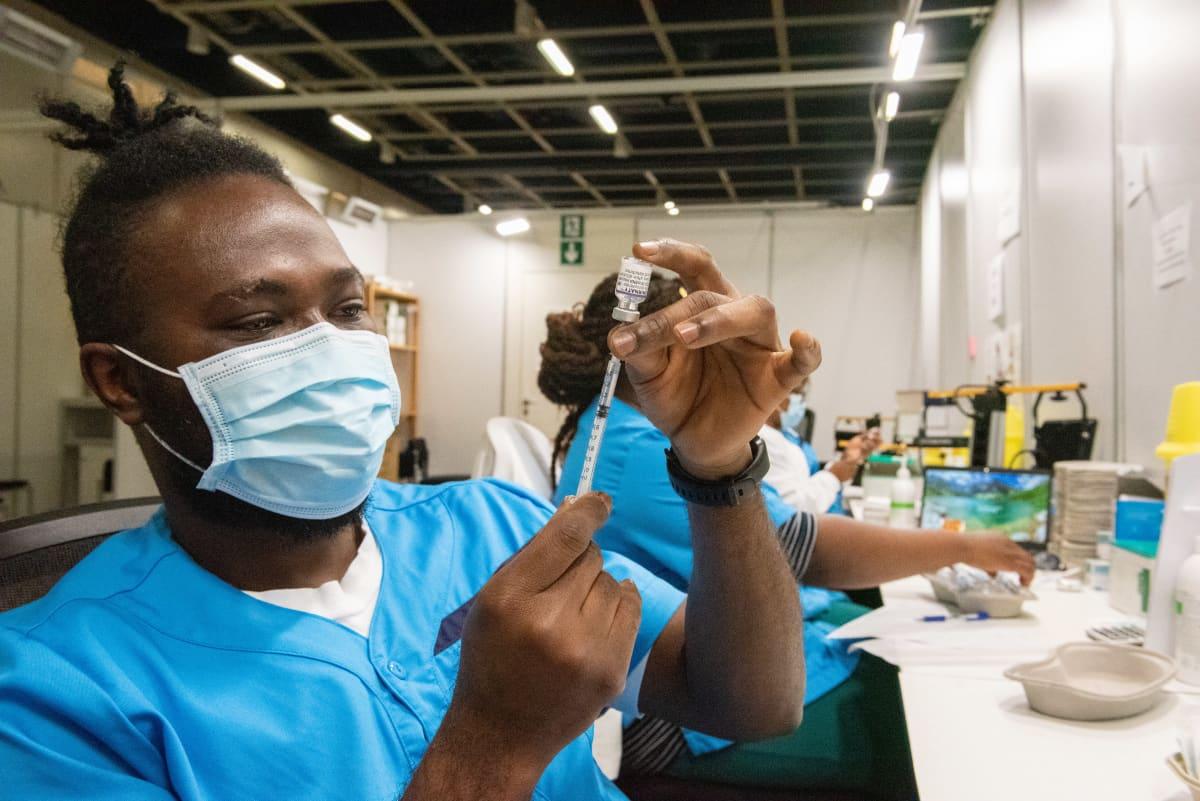 Sairaanhoitaja Francis Agbehiadzie valmisteli koronarokotetta Helsingin Messukekuksessa perjantaina.