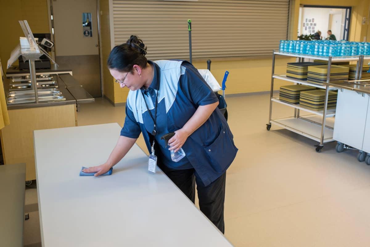 Palveluohjaaja Susanna Kaitajärvi pyyhkii pöytää koulun ruokalassa.