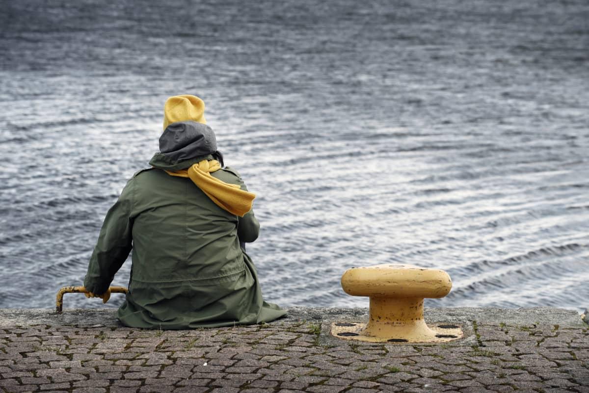 Nainen istuu yksin veden äärellä.