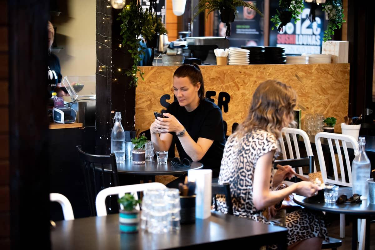 Outi Ellilä selaa puhelinta samalla kun istuu Hietalahden kauppahallin ravintolassa odottamassa lounasta.