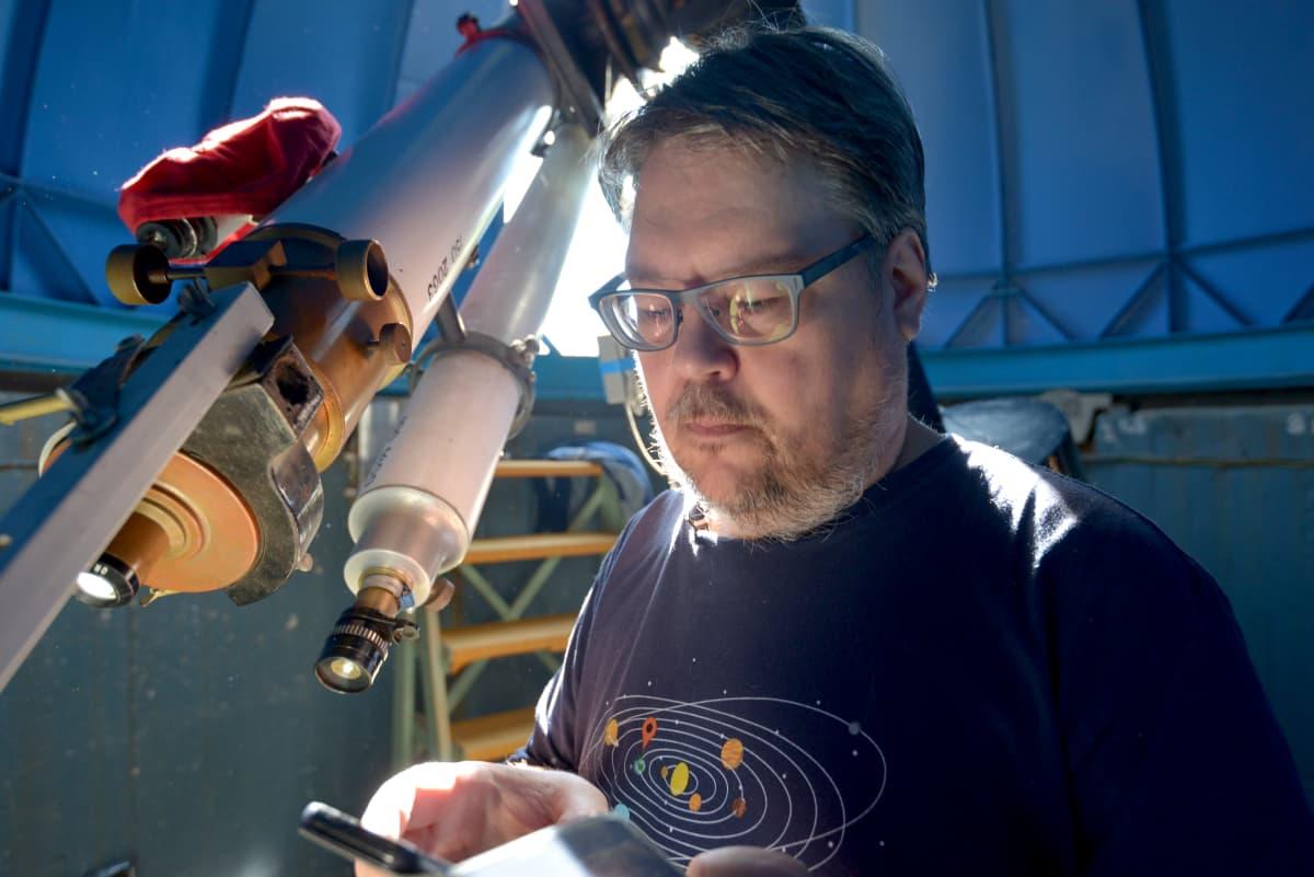 Tähtitieteen harrastaja Arto Oksanen valmistelee tähtitornissa kaukoputkea.