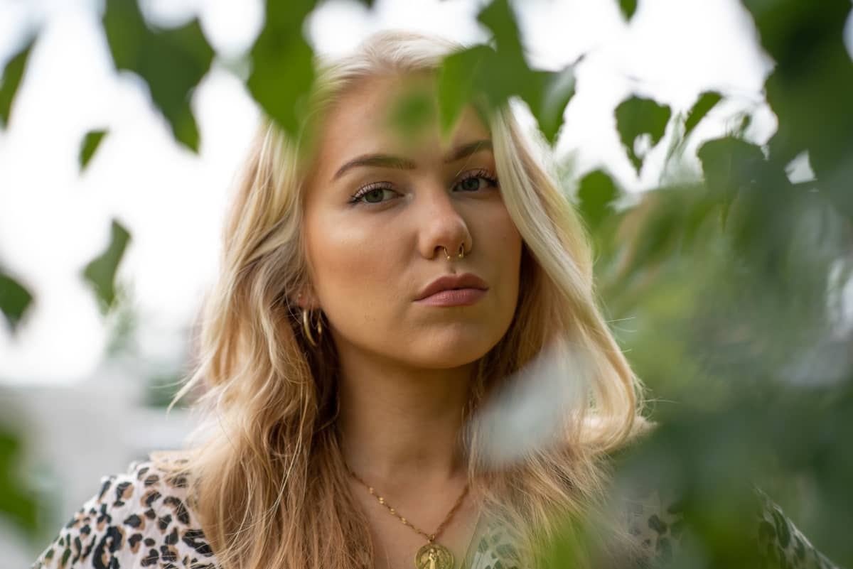 Evelina seisoo puistossa koivun oksien keskellä.