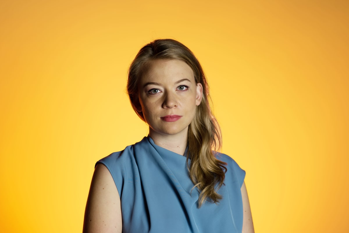 Iida Tikka kuvattuna studiossa keltaisella taustalla.