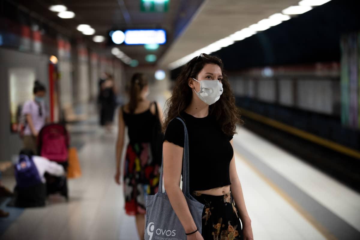Nainen odottaa metroa maski päässään.
