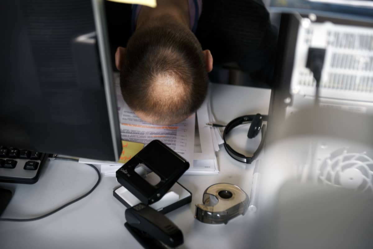 Työntekijä nojaa otsallansa työpöytään.
