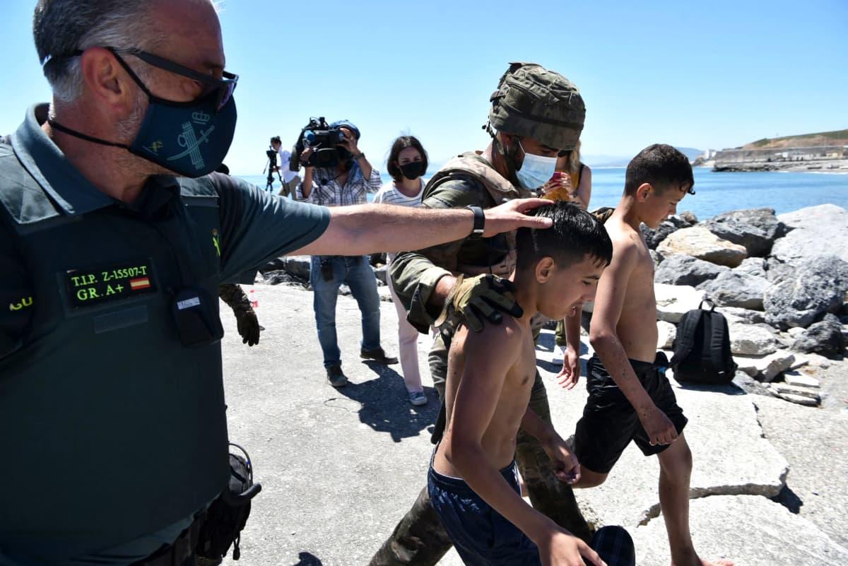 Sotilaat taluttavat maahan pyrkivää lasta Espanjalle kuuluvan Ceutan rannikolla.