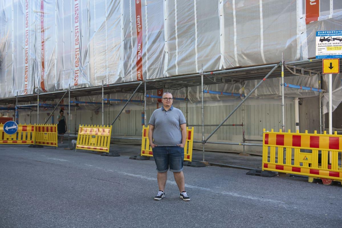 Benjamin Molini huputetun kotinsa edessä Haagassa. Talossa on käynnissä iso julkisivuremontti. enjamin Molini kotonaan Haagassa tietokoneen ääressä. Asunnon ikkunoista ei näy ulos eikä niitä saa auki, sillä talossa on käynnissä suuri julkisivuremontti.