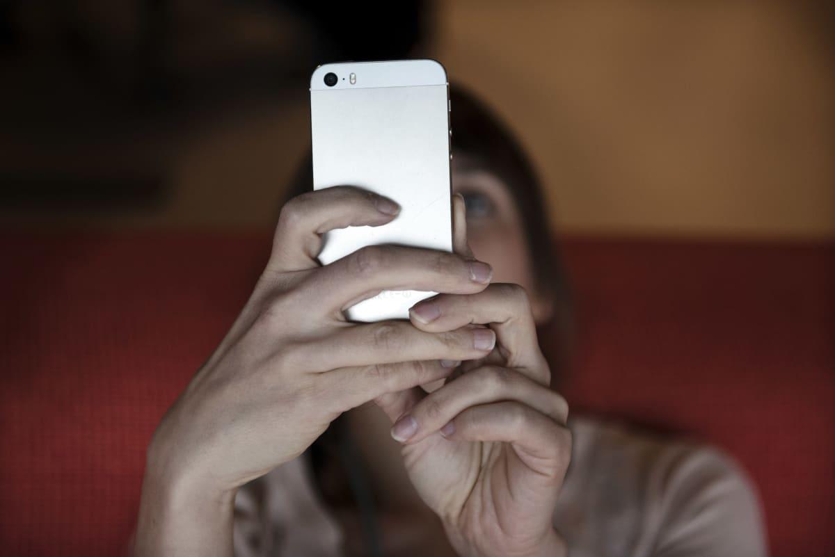 Nainen tuijottaa älypuhelintaan.