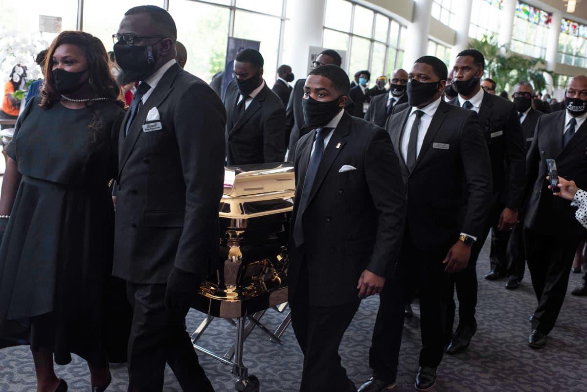 Saattajat kantavat arkkua  George Floydin hautajaisissa.