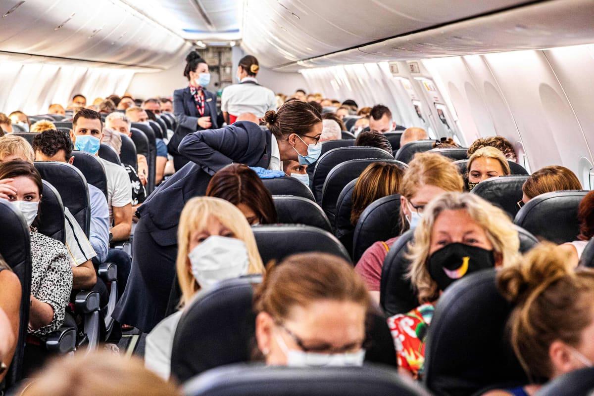 Kuvassa on täysi lentokone, jossa ihmiset käyttävät hengityssuojaimia.