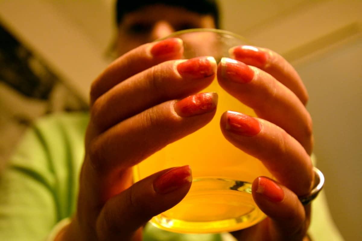 Nainen pitää kädessään limonadilasia.