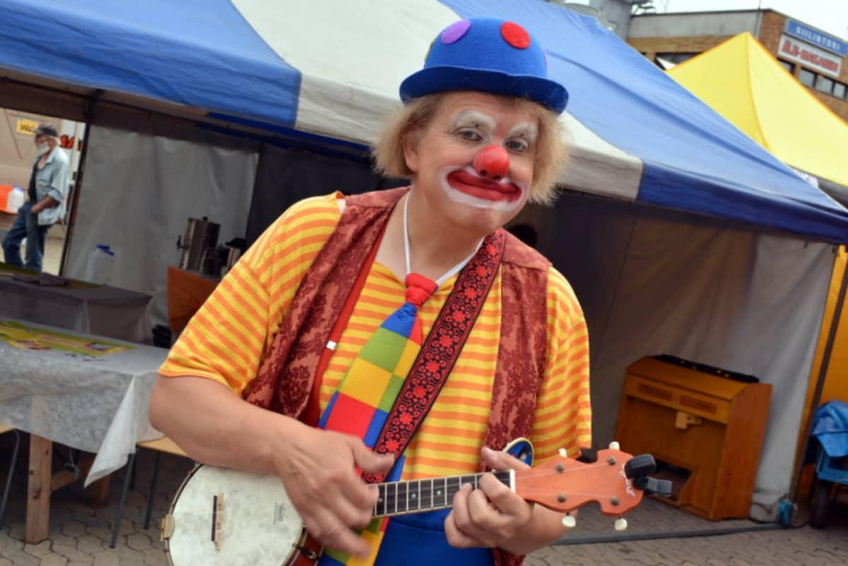 Klovni soittaa banjoa.