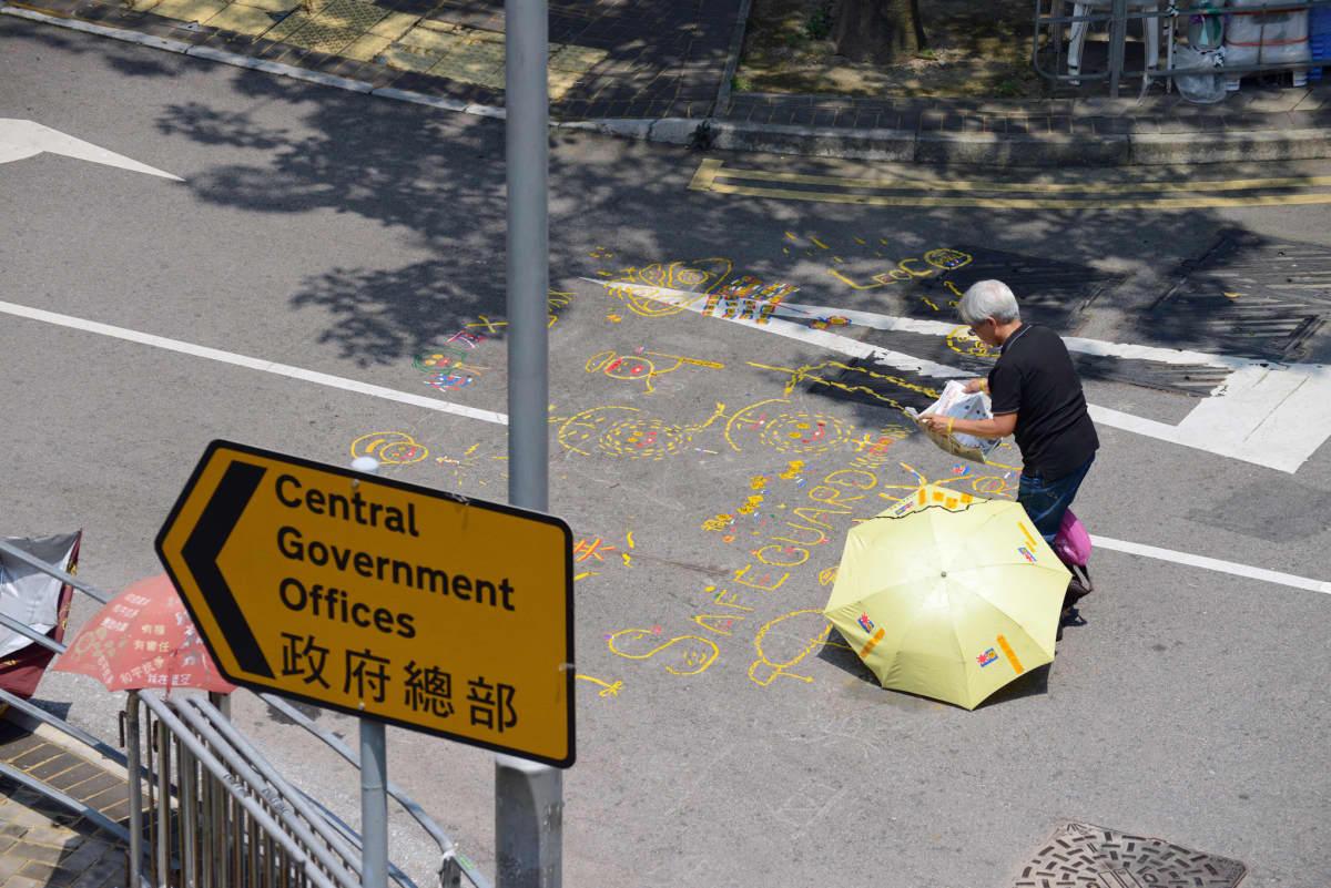 Mielenosoittaja hallintorakennuksen edessä.
