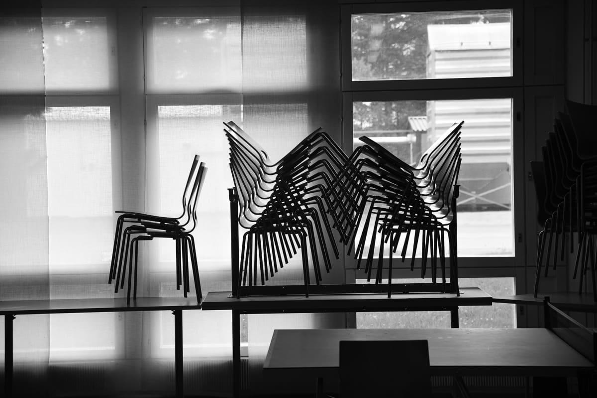 Mustavalkoisessa kuvassa tuolipino ikkunan edessä.