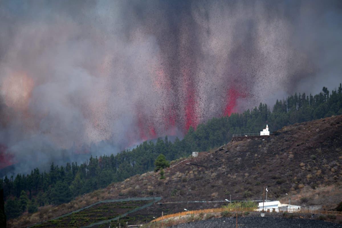 Tjock rök och vad ser ut som illröda flammor stiger upp ur en bergssluttning under ett vulkanutbrott på den spanska ön La Palma den 19 september 2021.