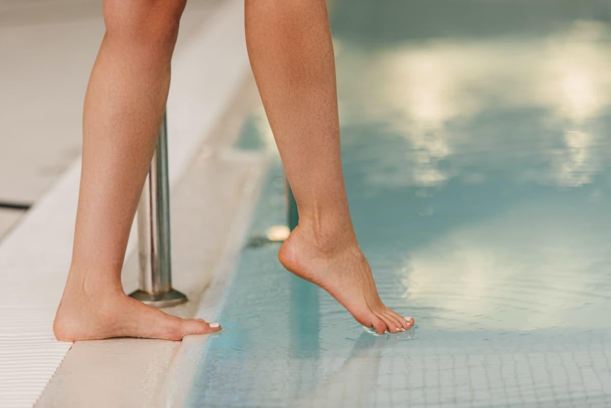 En person sticker sin tå i vattnet från simbassängskanten