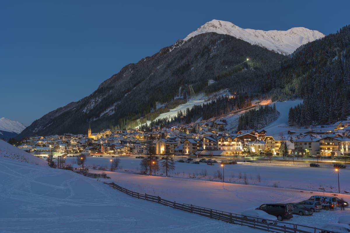 Ischglin kylä illan hämärässä taustallaan vuori