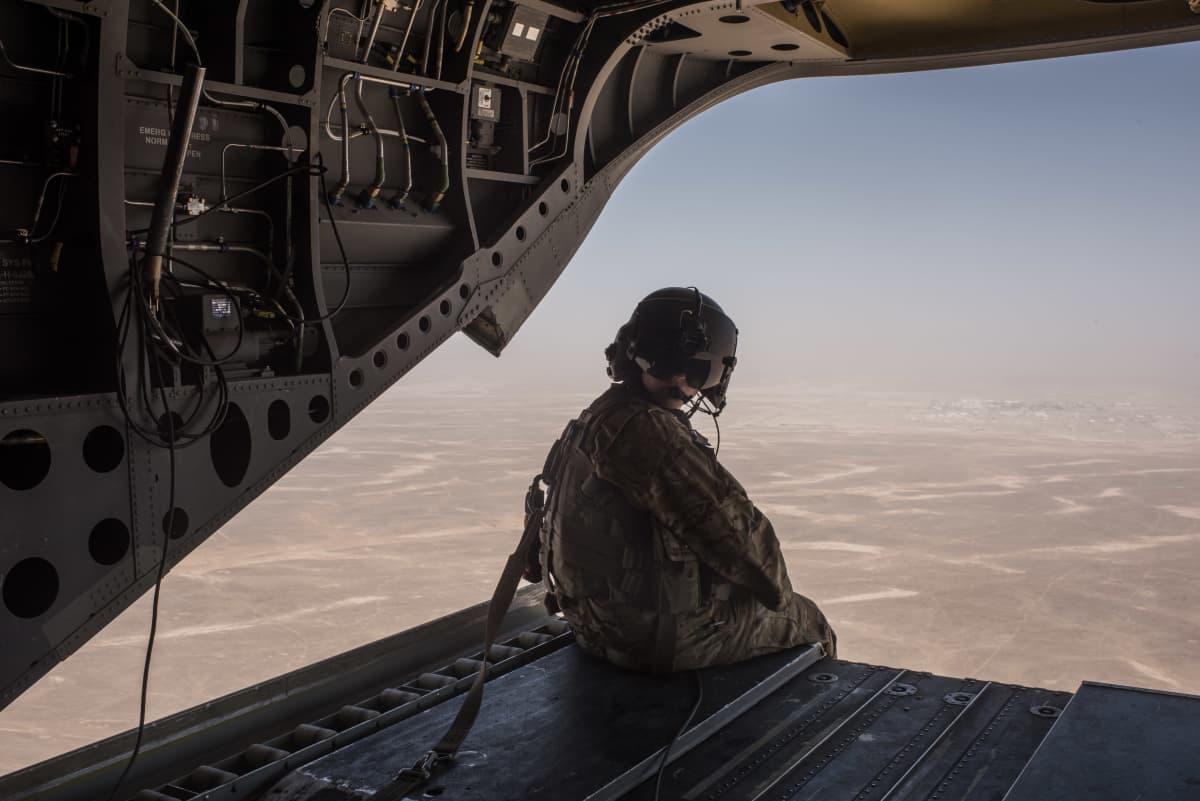 Yhdysvaltain merijalkaväen sotilas istuu helikopterin peräluukun reunalla ilmalennon aikana.