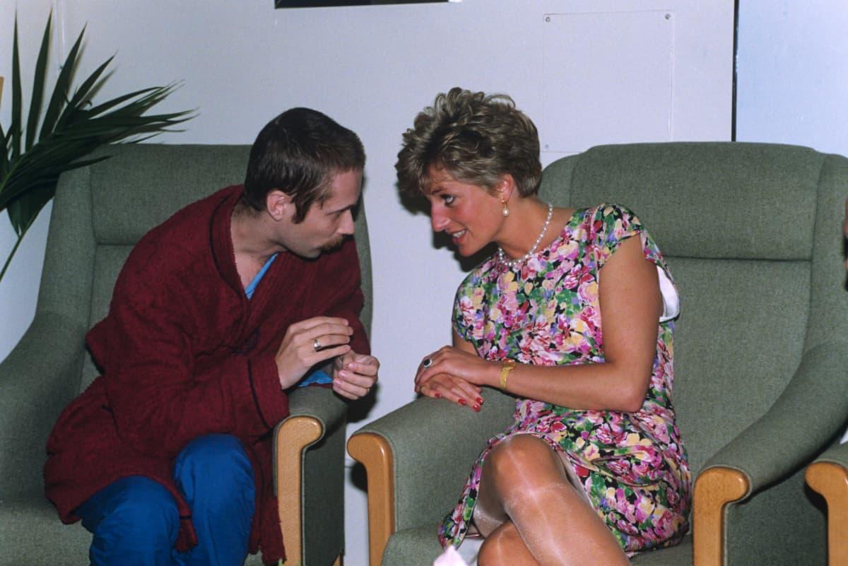 Aidsia sairastava mies ja Diana istuvat vierekkäin ja keskustelevat.