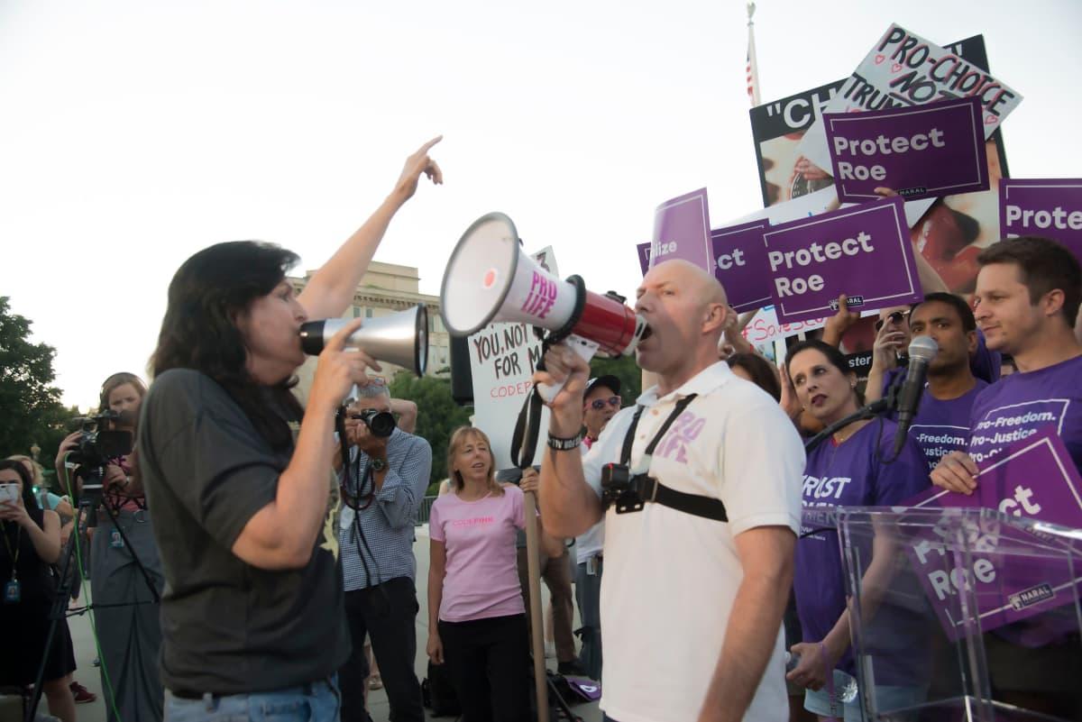 Nainen ja mies huutavat toisilleen lähietäisyydeltä megafonit kädessä.