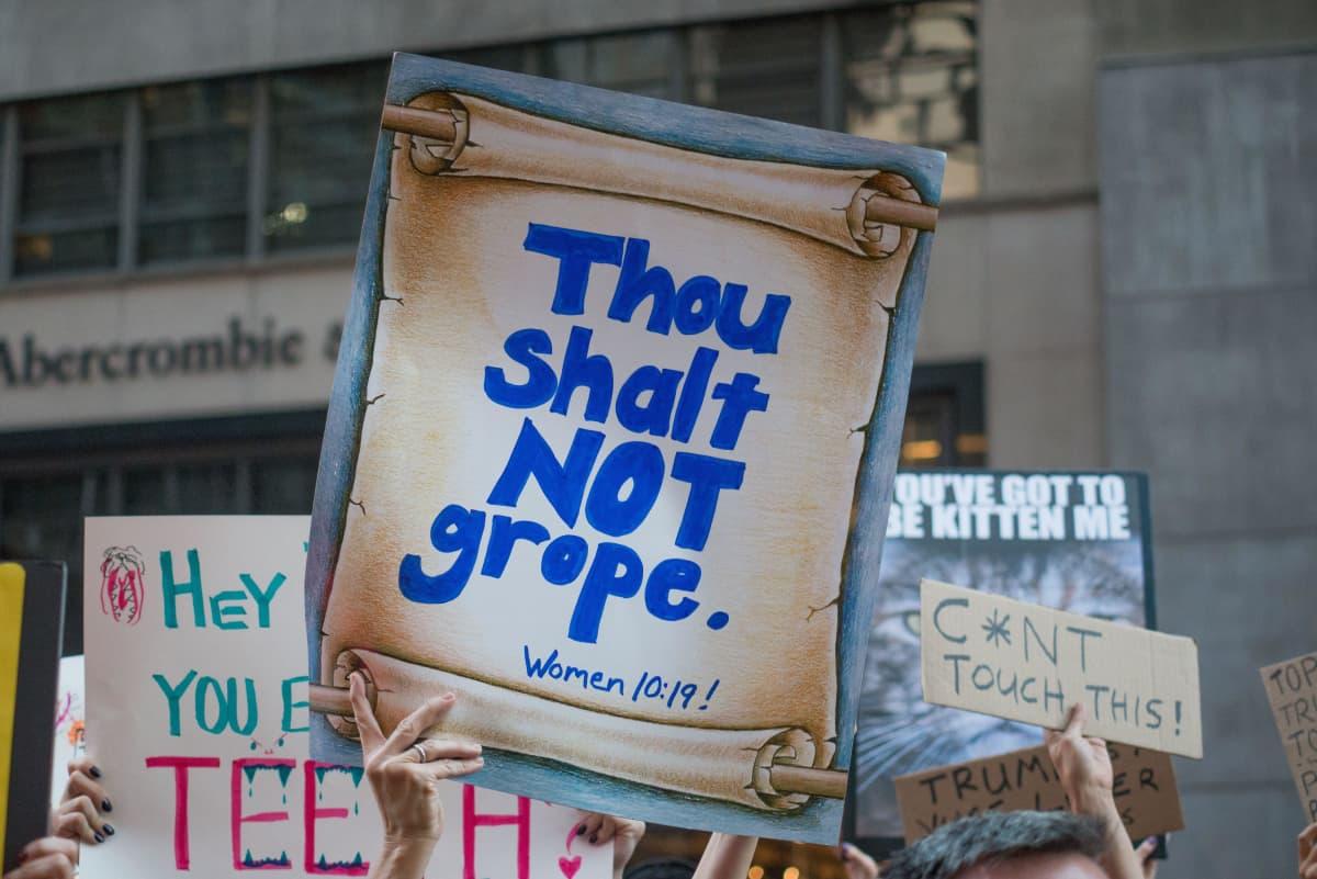 """""""Sinun ei pidä kouriman"""" luki seksuaalista ahdistelua vastustavan mielenosoituksen kyltissä New Yorkissa Trump Towerin edustalla lokakuussa 2016. Kommentti viittaa Trumpin rehentelyyn naisten haarovälin kourimisesta."""