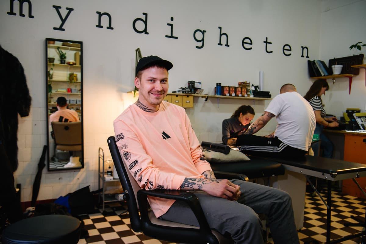 mies tuolissa tatuointistudiossa