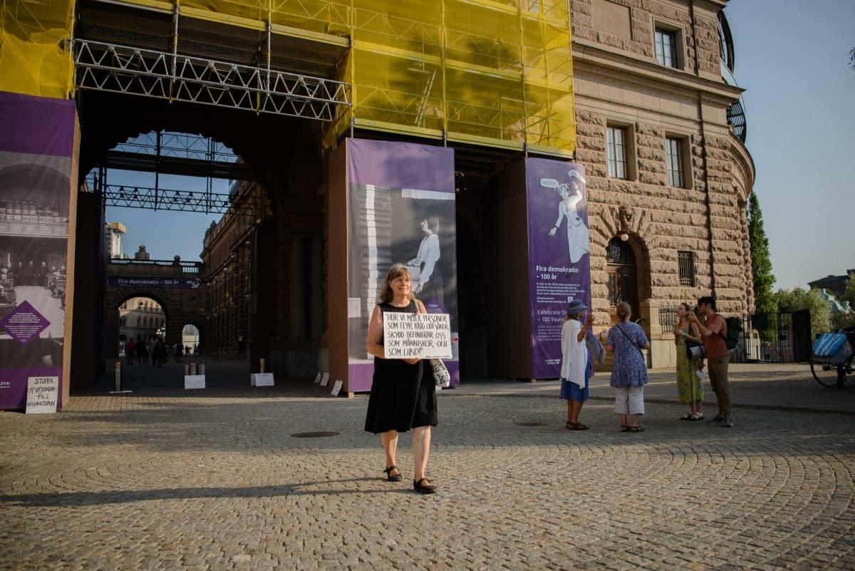 nainen kulkee kyltti kädessä Ruotsin valtiopäivätalon edustalla
