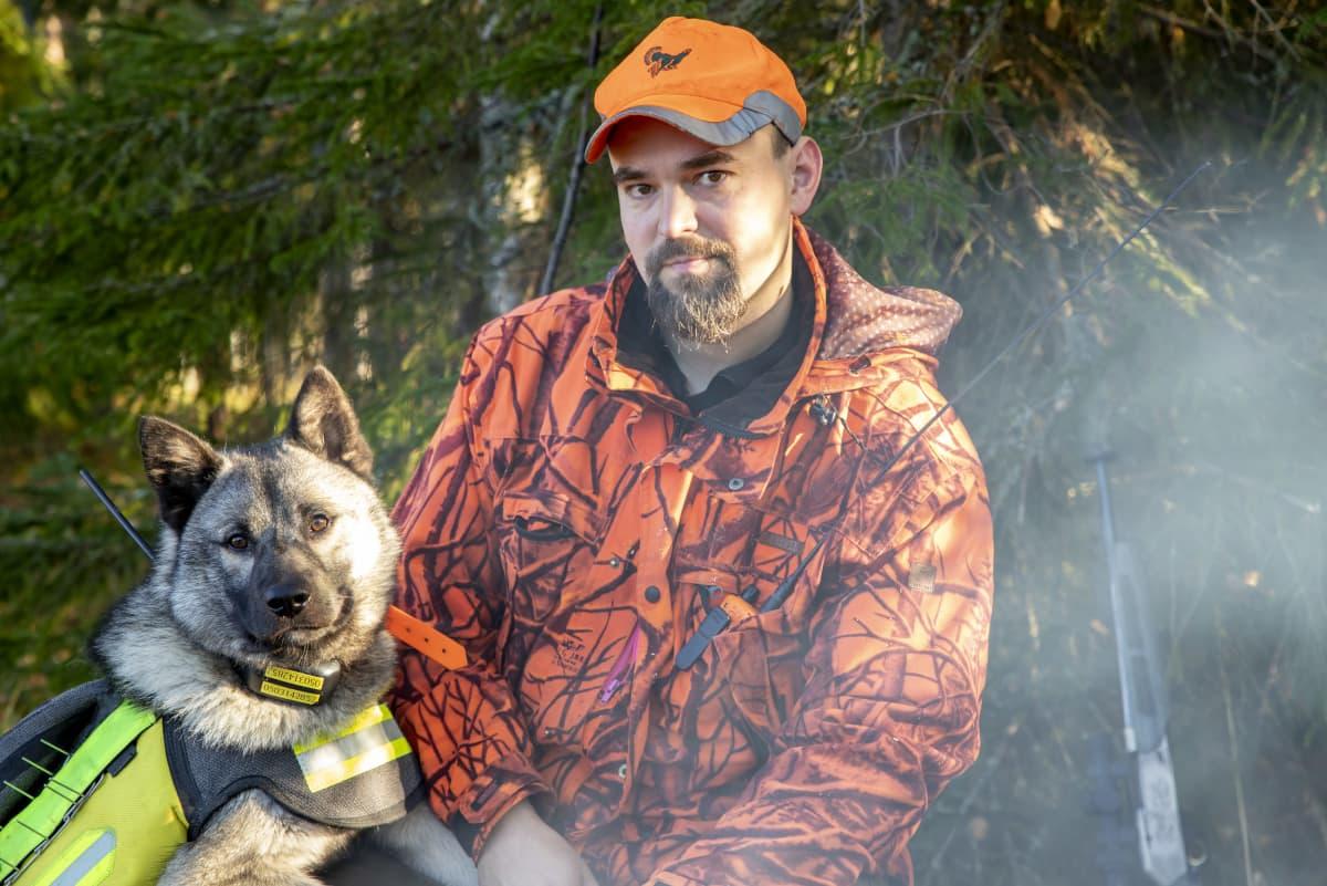 Jahtipäällikkö Ismo Ilomäki nuotiolla koiransa kanssa.