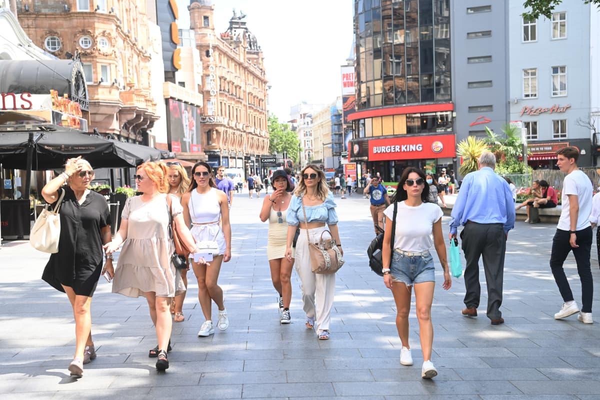 Maskittomia ihmisiä kävelemässä kadulla.