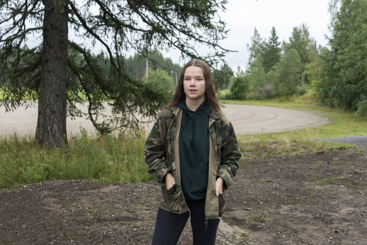 Tyttö seisoo kuusen ja urheilukentän edessä. Hänellä on päällään maastokuviollinen takki.