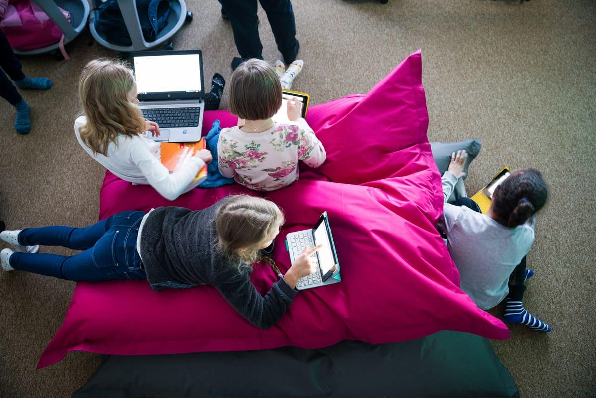 Lapsia tyynyn päällä tietokoneiden kanssa.