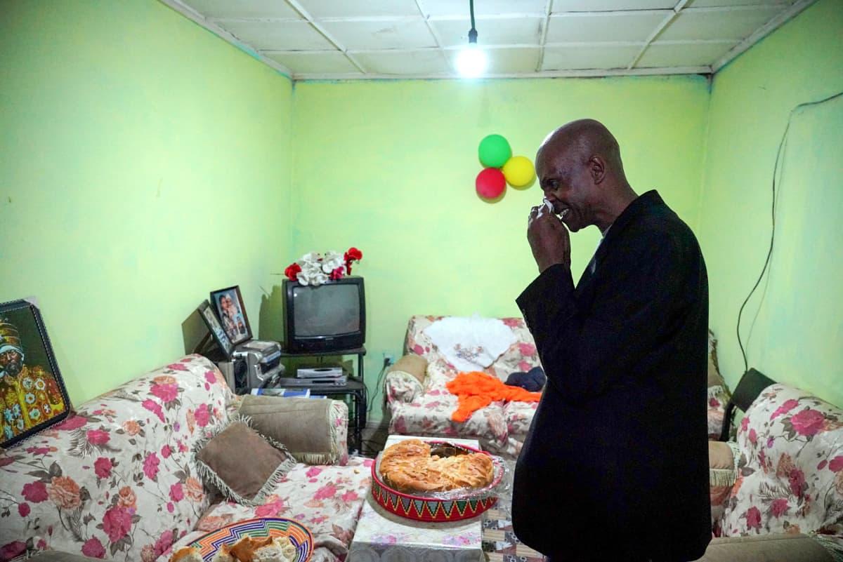 Eskinder Nega siunaa anoppinsa tuoman leivän ja jakaa siitä ystävilleen.