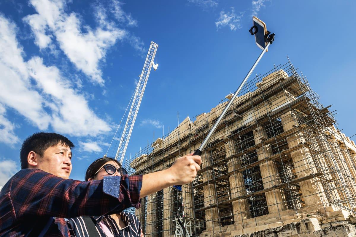 Kiinalaisturisteja ottamassa selfieitä Akropolis-kukkulalla.
