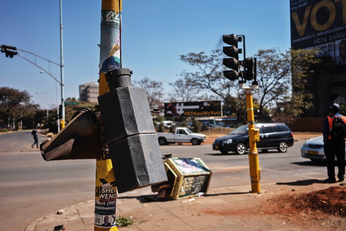 Rikottu liikennevalo ja roskis kadulla.