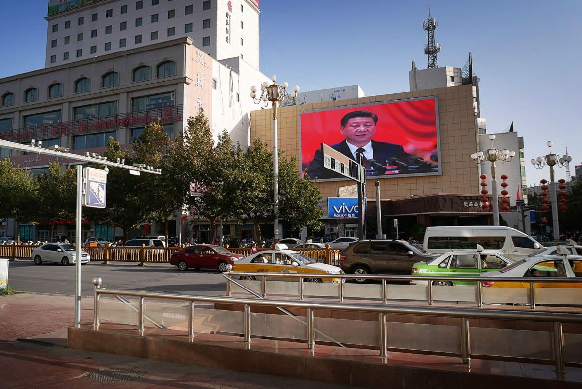 liikennettä, talon seinällä näytössä Kiinan presidentin Xi Jinpingin kuva