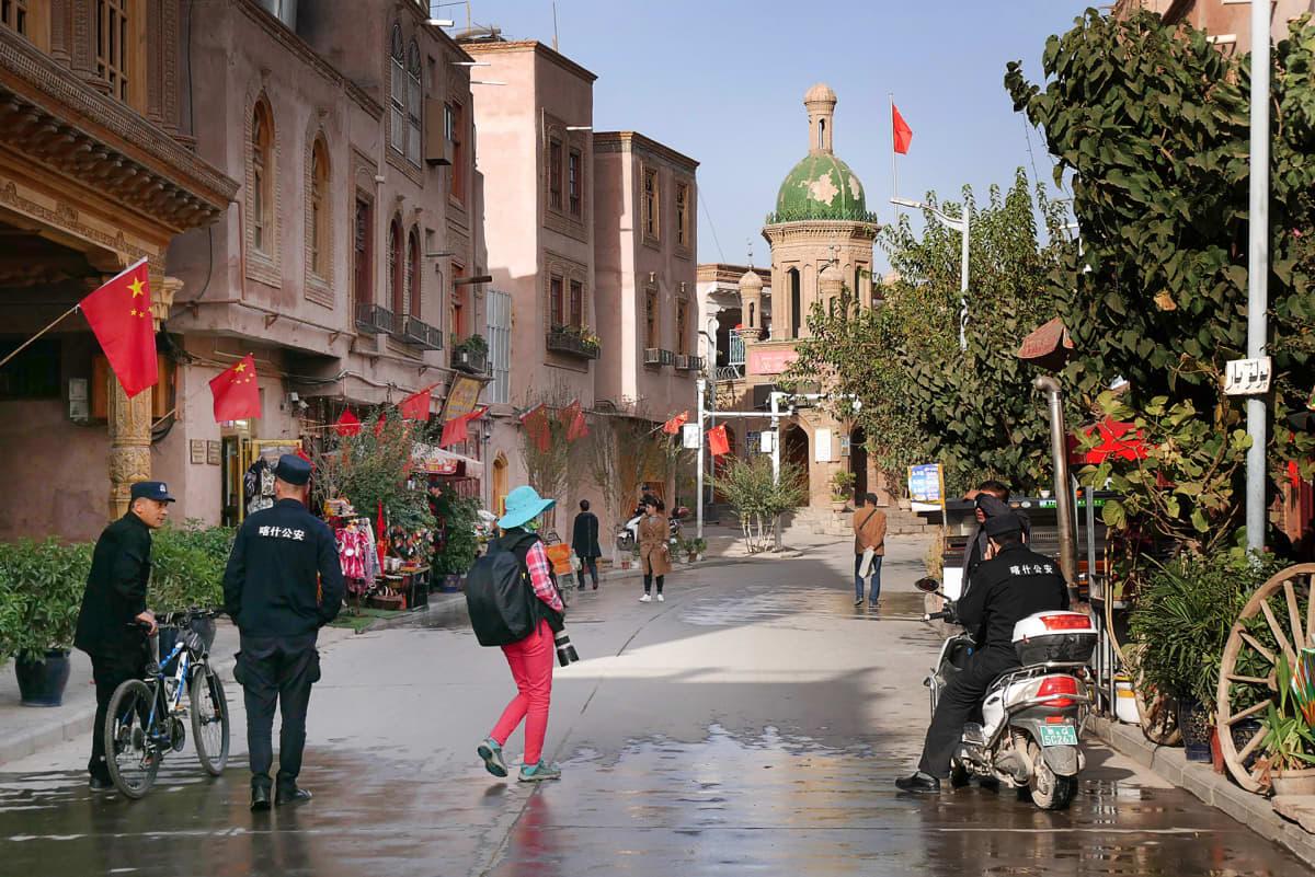 poliiseja ja hattupäinen siviilivaatteissa oleva ihminen kameran kanssa kadulla