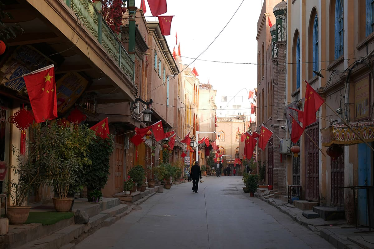 katu, jonka varrella olevien talojen seinissä on Kiinan lippuja