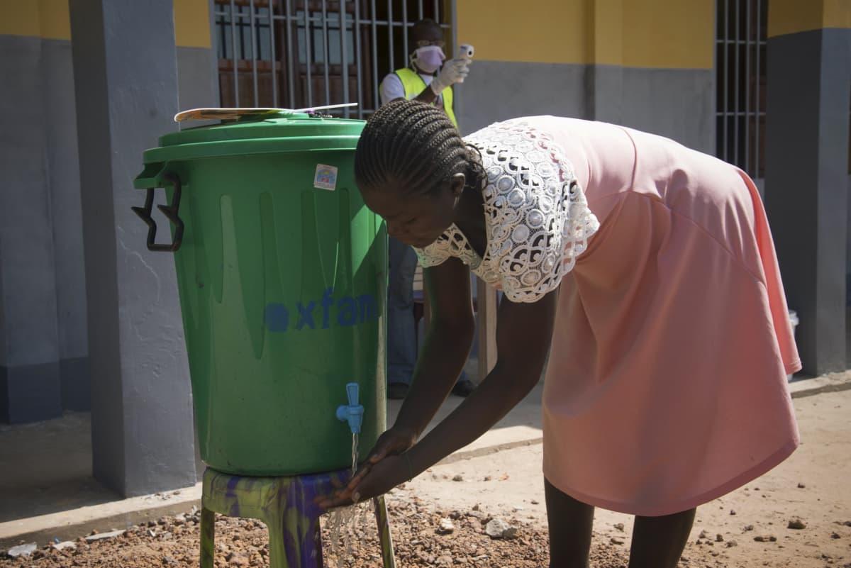 Nainen pesi käsiään välttääkseen ebolatartunnan. Kuva on otettu Kongon luoteisosassa Mbandakassa viime vuoden toukokuussa. Tuolloin aluetta vaivasi ebola.