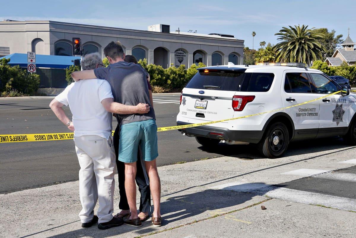 Ihmiset halaavat toisiaan Powayn kaupungissa sijaitsevan synagogan etupuolella. Heidän ja synagogan väliin on vedetty keltaiset poliisiteippaukset.