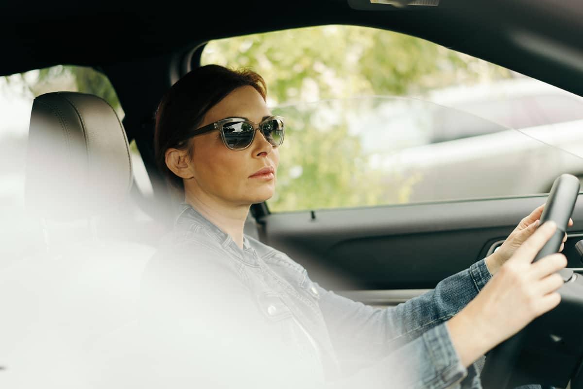 nainen ajaa autoa aurinkolasit päässä
