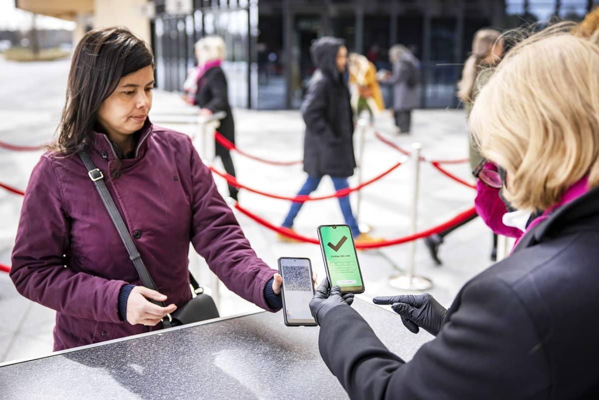 Matkailija esittää digitaalisen koronapassin virkailijalle.
