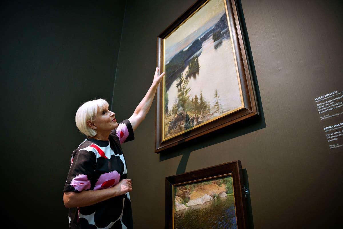 """Seija Paasonen Ateneumissa. Ylimpänä seinällä on Albert Edelfeltin teos """"Kaukolanharju auringonlaskun aikaan""""."""