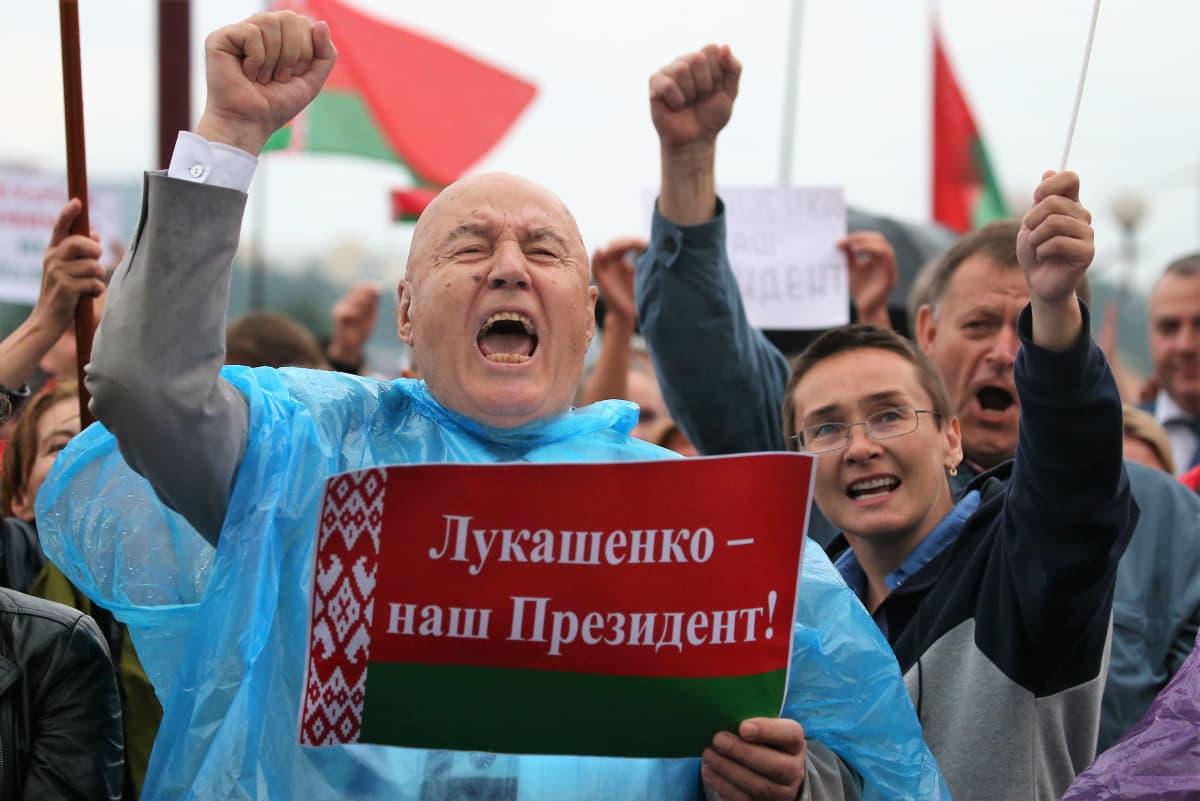 Mielenosoitusta Minskissä, Etualalla siniseen sadeviittaan pukeutunut mies pitää oikeaa kättään nyrkissä ja toisella Valko-Venäjän lipun väreillä koristeltua lappua, jossa lukee: Lukashenka - meidän presidenttimme!