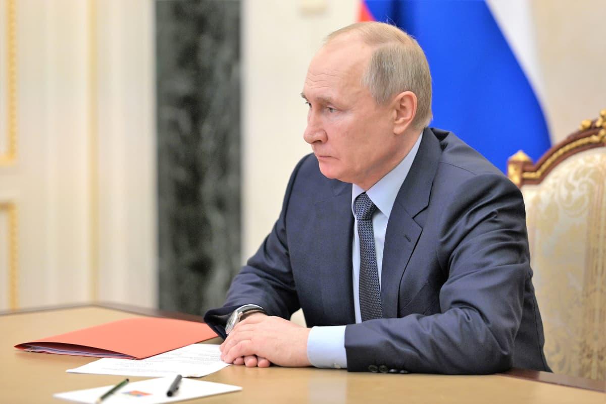 Putin istuu pöydän ääressä tummanharmaassa puvussa, vaaleansinisessä kauluspaidassa, tumma kravatti kaulassaan. Pöydällä edessä on pari paperia ja kynää ja oranssi kansio. Putinin ilme on vakava.