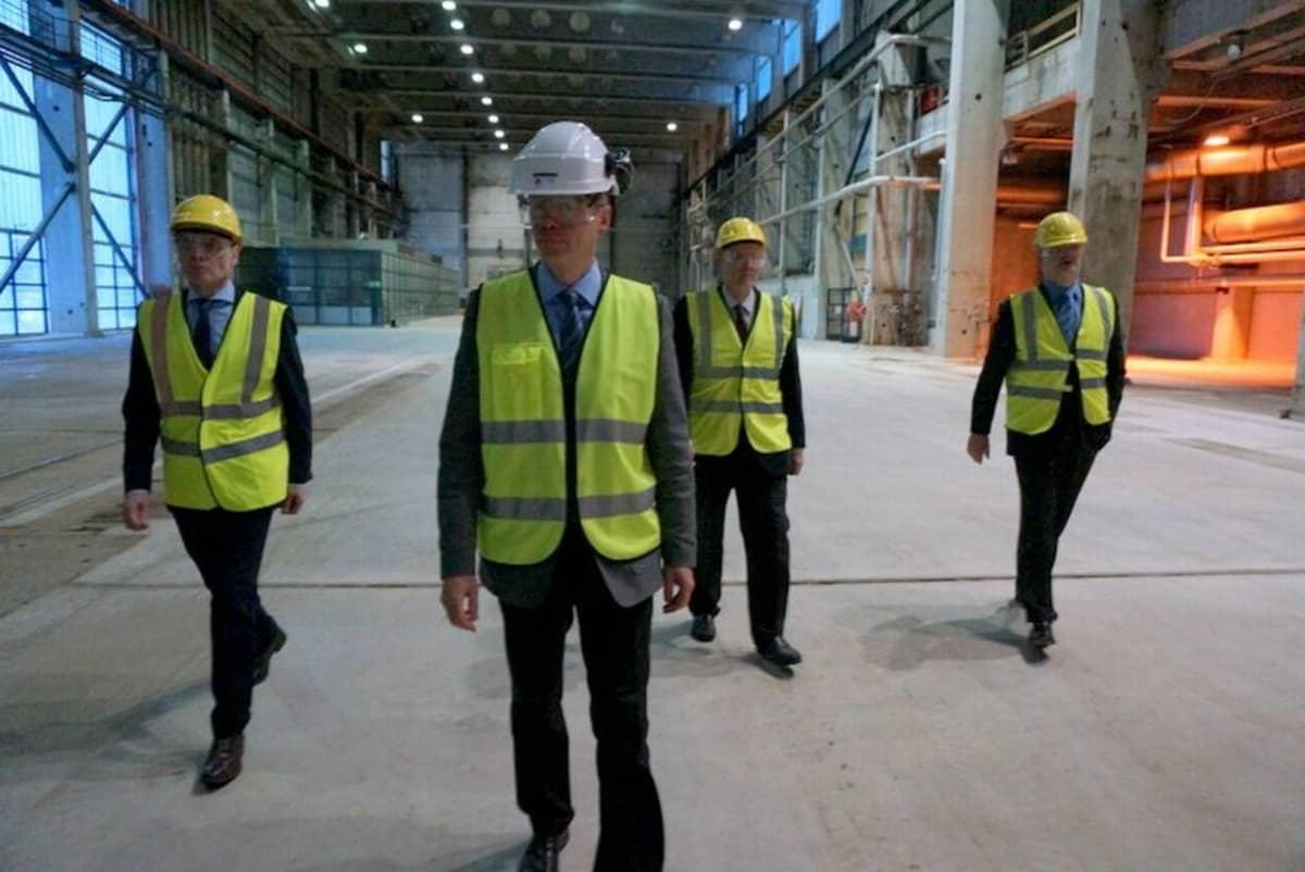 Neljä miestä kävelee tehdashallissa huomioliivit ja suojakypärät päällä.
